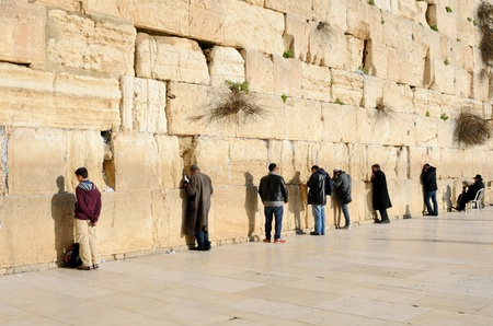 worshipers: JERUSALEM - FEBRUARY 19: Members of the Jewish faith pray at the western wall February 19, 2012 in Jerusalem, IL. The wall is one of the holiest sites in Judaism attracting thousands of worshipers daily.