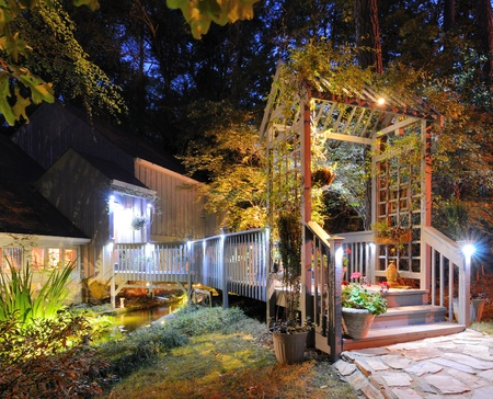 residential: House exterior with porch walkay over a pond and lighting in the woods