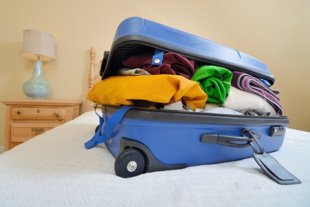 hotel bedroom: overflowing luggage on a bed