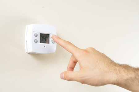 hands in the air: Hand changing thermostat  Stock Photo
