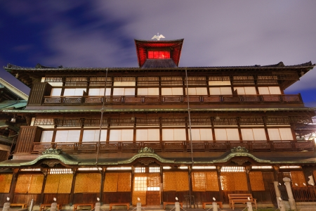 bathhouse: Dogo Onsen and the cityscape of Matsuyama, Japan. Dogo Onsen is one of the most famous hot spring bath houses in all of Japan.