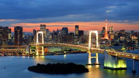Rainbow Bridge verspreid over Tokyo Bay met Tokyo Tower zichtbaar op de achtergrond. Redactioneel