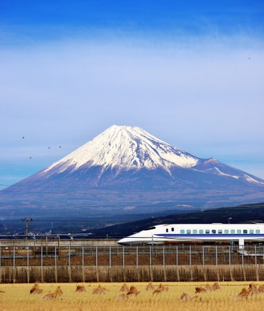 A bullet train passes below Mt  Fuji in Japan  photo