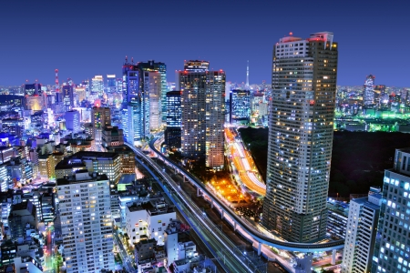 Dense buildings in Minato-ku, Tokyo Japan with Tokyo Sky tree visible on the horizon.