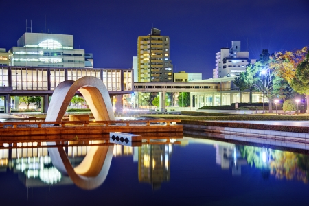 infamous: Cenotaph through which the Atomic Dome can be seen at at Peace Memorial Park in Hiroshima, Japan.