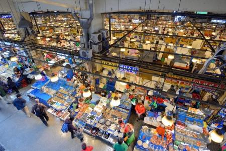 pesquero: SEUL - 18 de febrero: Vista a�rea de los compradores en Noryangjin Pesca Mercado Mayorista de 18 de febrero 2013 en Se�l, Corea del Sur. El mercado de 24 horas cuenta con m�s de 700 puestos de venta de pescados y mariscos frescos y secos.