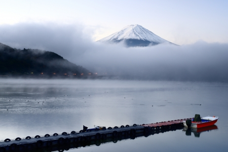 Mt. Fuji peaks from the clouds over Kawaguchi Lake in Japan.