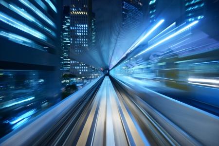 El desenfoque de movimiento de una ciudad y de túnel desde el interior de un monorraíl en movimiento en Tokio.