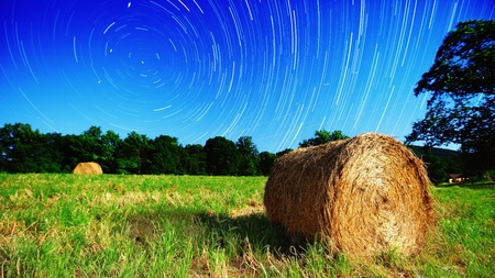 country side: Moonlit hay bale under star trails on a farm in North Georgia, USA.
