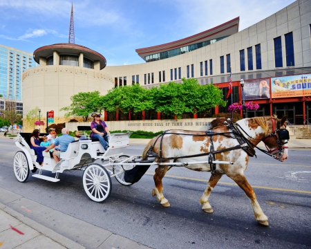 NASHVILLE - JUNE 14: Tourists in a horse-drawn carriage pass the Country Music Hall of Fame and Museum June 14, 2013 in Nashville, TN. The museum opened in 1961 and preserves the history of country music. Editöryel