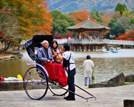 NARA, JAPAN - NOVEMBER 18: A rickshaw runner enthusiastically explains the ride to tourists November 18, 2012 in Nara, JP. Rickshaws are commonly believed to have been invented in Japan in the 1860s.