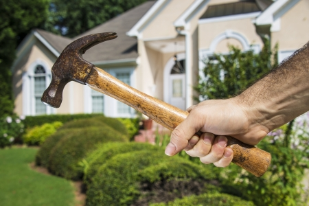 Mans hand holding hammer in front of a house indicating home improvement and maintenance. Stok Fotoğraf