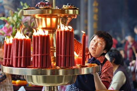tends: TAIPEI, TAIWAN - JANUARY 11: A woman tends to candles at Longshan Temple January 11, 2013 in Taipei, TW. The temple was built in 1738 by settlers from Fujian. Editorial