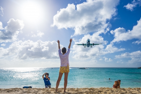 sint: PHILIPSBURG, SINT MAARTEN - DECEMBER 30, 2013: A commercial jet approaches Princess Juliana airport above onlooking spectators. The short runway gives beach goers close proximity views of the planes.