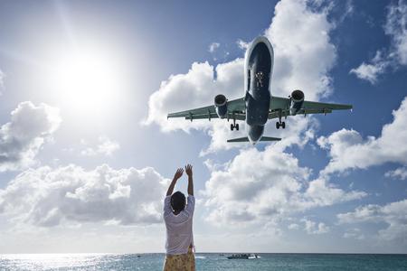 juliana: PHILIPSBURG, SINT MAARTEN - DECEMBER 30, 2013: A commercial jet approaches Princess Juliana airport above onlooking spectators. The short runway gives beach goers close proximity views of the planes.