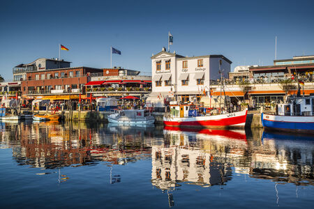 alte: WARNEMUNDE, GERMANY - SEPTEMBER 13, 2013: Warnemunde cityscape on Alte Strom old channel. Founded in 1200, the once sleepy fishing village has grown into a prominent seaside resort town.