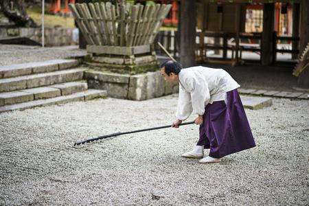 NARA, JAPAN - NOVEMBER 18, 2012: A Shinto Priest rakes a gravel Zen Garden at Kasuga-Taisha Shrine. The gardens have a long history in Japan and the surroundings are used to aid meditation.