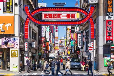 TOKYO, JAPAN - MARCH 15, 2014: Crowds walk below the Kabuki-cho signs. The area is a renown nightlife and red-light district.