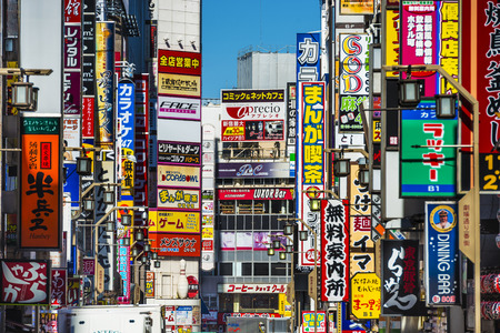 TOKYO, JAPAN - MARCH 15, 2014: Signs densely line an alleyway in Kabuki-cho. The area is a renown nightlife and red-light district.