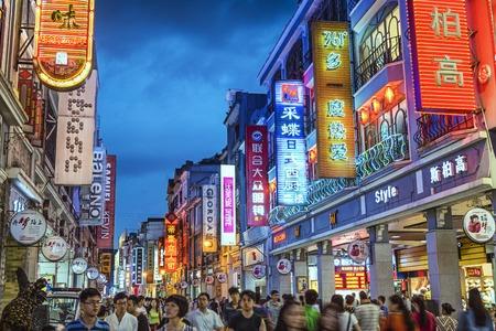 atracci�n: GUANGZHOU, CHINA - 25 de mayo 2014: Los peatones pasan por Shangxiajiu Pedestrian Street. La calle es el principal distrito comercial de la ciudad y una gran atracci�n tur�stica. Editorial