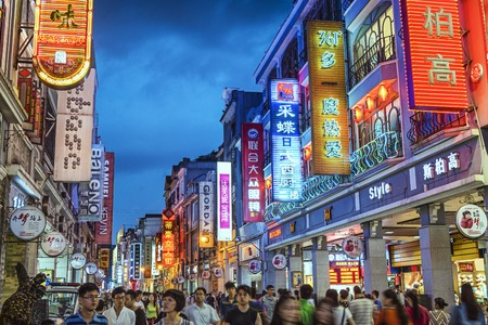 guangzhou: GUANGZHOU, CHINA - MAY 25, 2014: Pedestrians pass through Shangxiajiu Pedestrian Street. The street is the main shopping district of the city and a major tourist attraction.