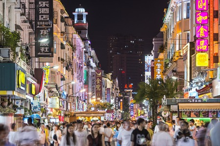 XIAMEN, CHINA - JUNE 11, 2014: Pedestrians stroll down Zhongshan Road at night. The road is the main commercial street in Xiamen and parts have been fully pedestrianized. Redakční
