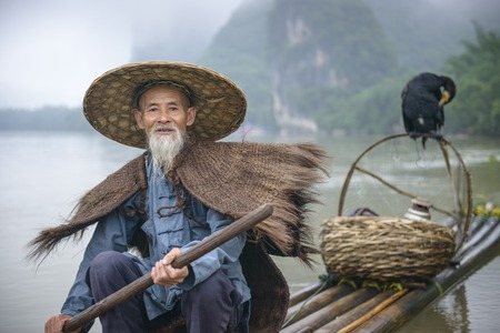 villager: Cormorant fisherman and his bird on the Li River in Yangshuo, Guangxi, China