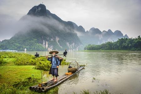 Cormorant fisherman and his birds on the Li River in Yangshuo, Guangxi, China  스톡 콘텐츠