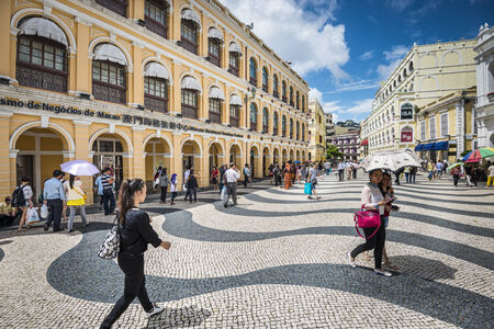 MACAU, CHINA - MAY 21, 2014: Pedestrians stroll down Senado Square. The territory was the last European colony in Asia and the architecture is inspired by the former Portuguese rule.