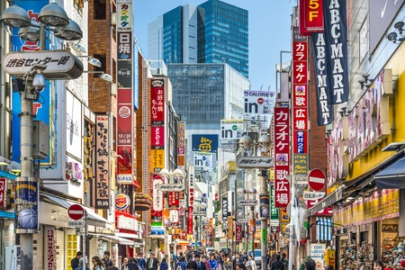daylight: TOKYO, JAPAN - MARCH 31, 2014: Pedestrians stroll down Shibuya Cener-gai. The area is a popular destination for fashion and shopping.