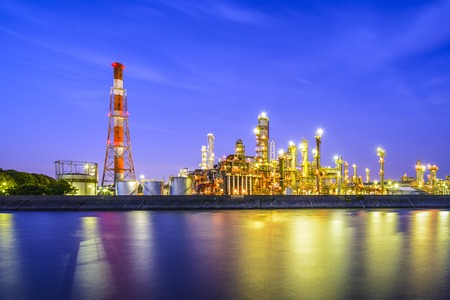 Oil refineries line a river in Yokkaichi, Japan. The city has been a center for the chemical industry since the 1930s. Stock Photo