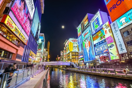osaka: OSAKA, JAPAN - NOVEMBER 25, 2012: Tourists watch the famed advertisements of Dotonbori. With a history reaching back to 1612, the districtis now one of Osakas primary tourist destinations.