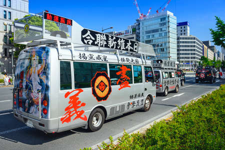 nationalists: OSAKA, JAPAN - MAY 4, 2014: A caravan of a Uyoku dantai vans drives through Osaka. The right wing groups are well known for propaganda vehicles which broadcast nationalistic slogans via loudspeakers.