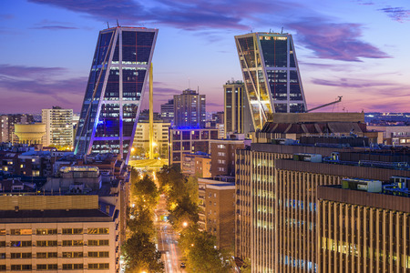 Madrid, Spain financial district skyline at twilight viewed towards the Gate of Europe Plaza.