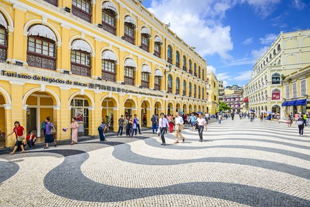 squares: MACAU, CHINA - MAY 21, 2014: People enjoy Senado Square. The territory was the last European colony in Asia and the architecture is inspired by the former Portuguese rule. Editorial