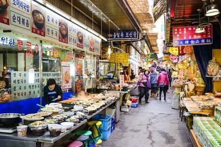 ソウル、韓国 - 2013 年 2 月 14 日: 買い物客は東大門市場を通過します。市場は、ショッピングや観光に人気の場所です。