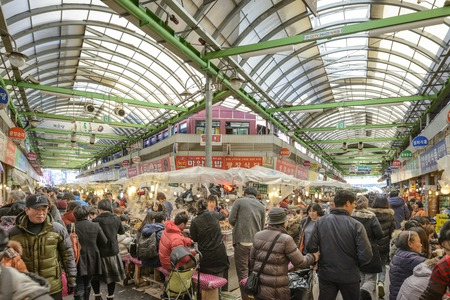 traditional culture: SEOUL, SOUTH KOREA - FEBRUARY 16, 2013: Shoppers pass through Gwangjang Market. The market dates from 1905 and offers a glimpse into traditional markets of the country.