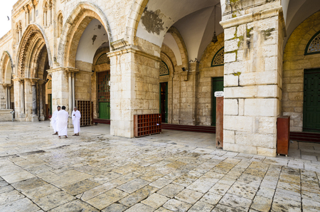 JERUSALEM, ISRAEL - FEBRUARY 20, 2012: Pilgrims stand and chat at Al Aqsa Mosque. The mosque is the third holiest site in Islam. Imagens - 34587654