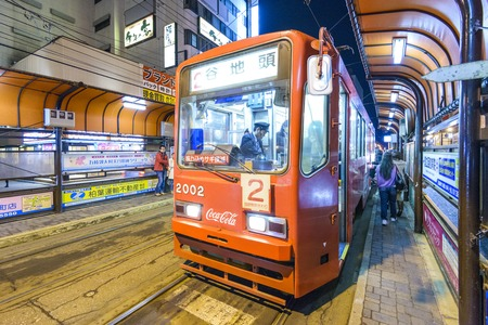 local landmark: HAKODATE, JAPAN - OCTOBER 25, 2012: Passengers alights from the tram. The tram originates from 1897 and is a local landmark as well as an efficient means of transit.