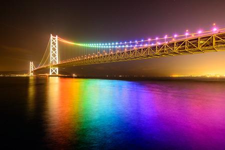 rainbow bridge: Rainbow lights on Akashi Ohashi (Pearl Bridge) in Kobe, Japan. Stock Photo