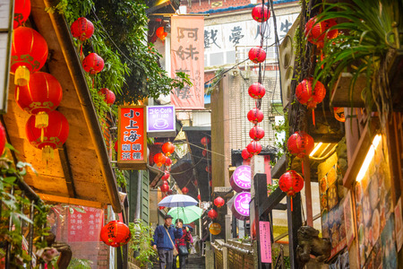 JIUFEN, TAIWAN - JANUARY 17, 2013: Tourists stroll through quaint alleys of Jiufen. The town is a tourist attraction renown for a its unique atmosphere.