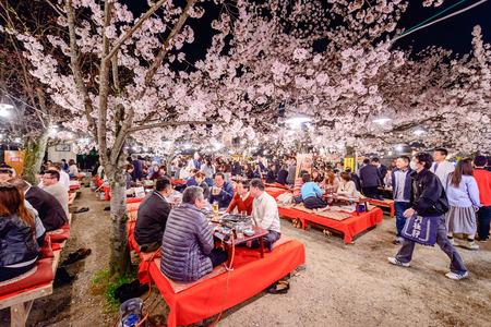 coincidir: Kyoto, Japón - 03 de abril 2014: La gente disfruta de la temporada de primavera al participar en festivales nocturnos Hanami en Maruyama Park. Los festivales anuales coinciden con la floración de temporada de los cerezos en flor.