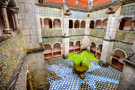 the pena national palace: SINTRA, PORTUGAL - SEPTEMBER 19, 2014: A decorative plant sits at the center of the Pena National Palace interior courtyard.