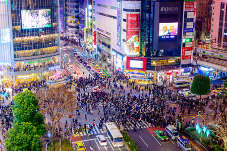 TOKYO, JAPAN - DECEMBER 23, 2012: Pedestrians cross at Shibuya Crossing. It is one of the worlds most famous scramble crosswalks.