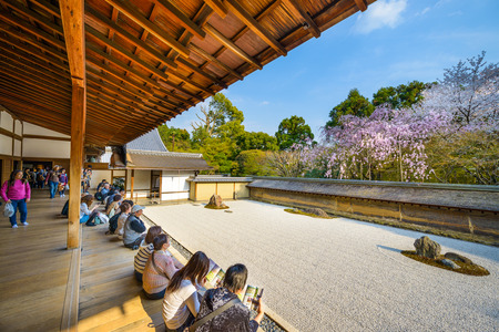 buddhist temple roof: KYOTO, JAPAN - APRIL 9, 2014: Tourists sit and observe the spring cherry trees of Ryoan-ji Temple. The garden is considered one of the finest surviving examples of dry landscapes.