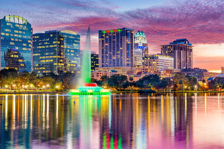 night view: Orlando, Florida, USA skyline at dusk on Eola Lake.