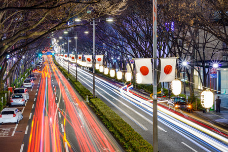 Harajuku Tokyo Japan traffic flows below Japanese flags at night. Lanterns read