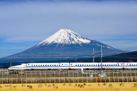 JAPAN  DECEMBER 14 2012: A Shinkansen bullet train passes below Mt. Fuji in Japan.