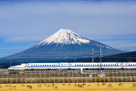JAPAN  DECEMBER 14 2012: A Shinkansen bullet train passes below Mt. Fuji in Japan.