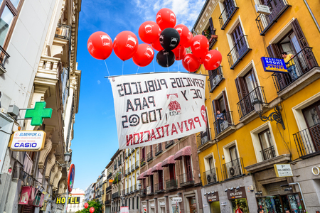 protestors: MADRID, SPAIN - OCTOBER 17, 2014: A banner carried by balloons protests the privatization of state-owned airport operator Aena Aeropuertos.